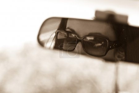 Photo for The face of a young woman driving as seen in the rear view mirror. - Royalty Free Image