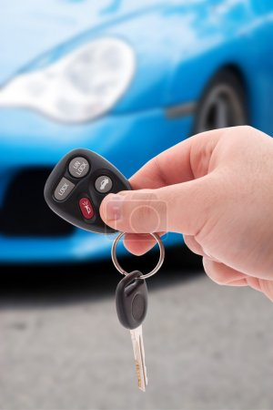 Photo for A hand holding car keys and a remote control for keyless entry. - Royalty Free Image