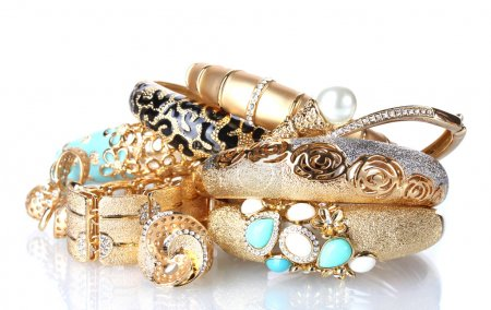 Beautiful golden bracelets and rings isolated on white