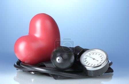 Photo pour Tonomètre noir et coeur sur fond bleu - image libre de droit