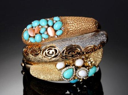 Foto de Hermosas pulseras de oro sobre fondo gris - Imagen libre de derechos