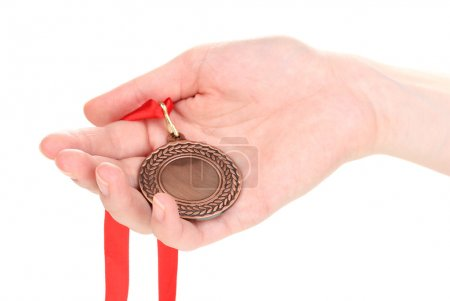 Bronze medal in hand isolated on white