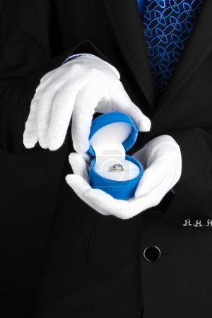 Man's hands holding ring in box