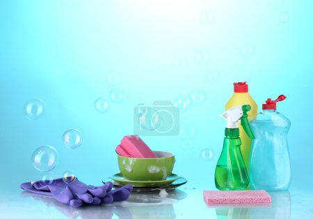 Photo for Washing dishes. Cleaning products on bright blue background - Royalty Free Image