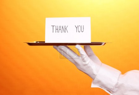 Photo for Hand in glove holding silver tray with card saying thank you on yellow background - Royalty Free Image