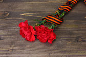 Carnations and St. Georges ribbon on grey wooden background