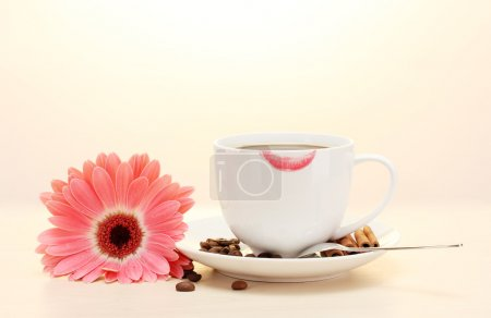 Photo for Cup of coffee with lipstick mark and gerbera beans, cinnamon sticks on wooden table - Royalty Free Image