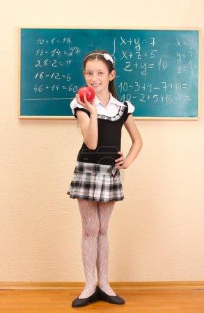 Beautiful little girl in school uniform with apple in class room