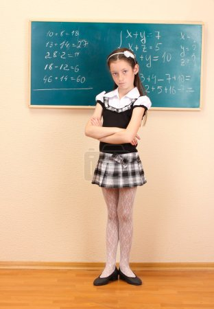 Beautiful little girl in school uniform in class room