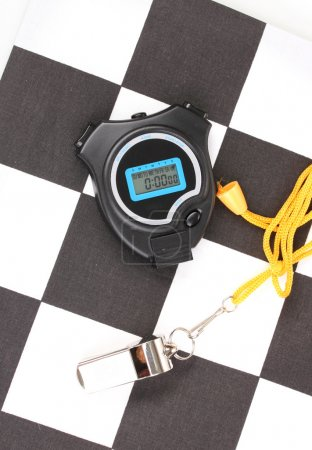 Checkered finish flag with whistle and stopwatch close-up