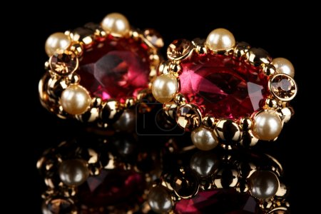 Photo for Beautiful gold earrings with rubies and pearls on black background - Royalty Free Image