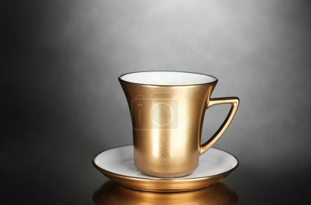 Golden cup of coffee on gray background