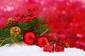 Vánoční koule a zelený strom na sněhu na červené