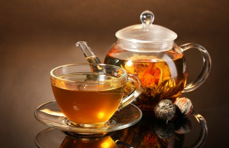 Théière en verre et tasse à thé vert exotique sur une table en bois sur backgro brun