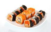 Lahodné sushi na desce izolovaných na bílém