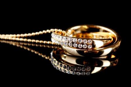 Photo pour Pendentif en forme d'anneaux avec gemme sur noir - image libre de droit