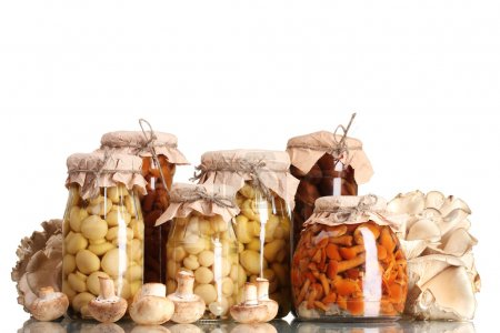 Delicious marinated mushrooms in the glass jars and raw champignons isolate
