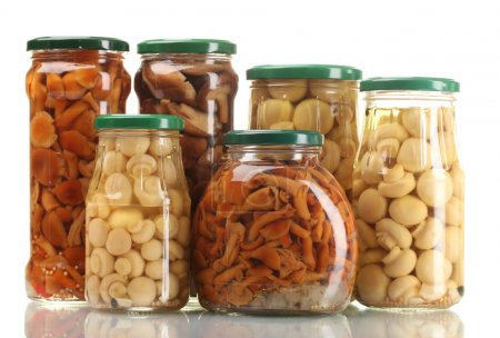 Different glass jars of marinated mushrooms isolated on white