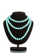 Beautiful necklace of blue pearls on a mannequin isolated on white