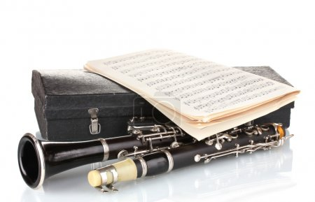 Antique clarinet, case and notebook with notes isolated on white
