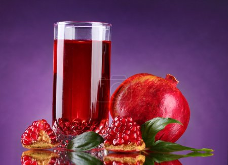 Ripe pomergranate and glass of juice on purple background