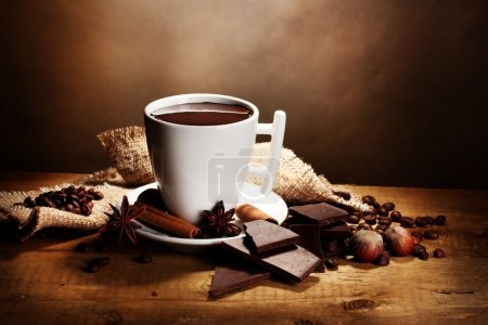 Cup of hot chocolate, cinnamon sticks, nuts and chocolate on wooden table o