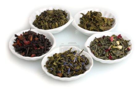 Photo pour Feuilles de thé sèches vertes et noires dans des assiettes isolées sur blanc - image libre de droit