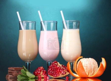 Photo pour Milk shakes aux fruits et chocolat sur fond bleu - image libre de droit