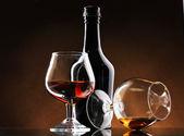 Pohár pálinkát és egy üveg barna háttér