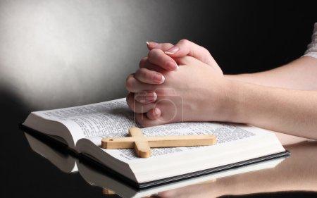 Photo pour Mains féminines sur la bible sainte russe ouverte sur fond noir - image libre de droit