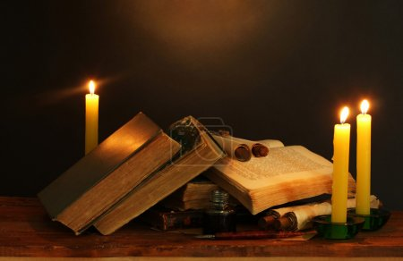 Old books, scrolls, ink pen inkwell and candles on wooden table on brown ba