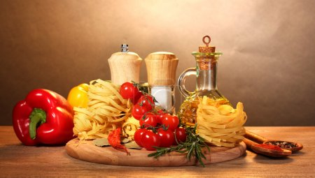 Photo for Noodles in bowl, jar of oil, spices and vegetables on wooden table on brown background - Royalty Free Image