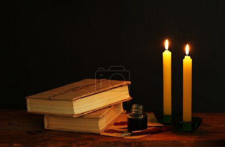Old books, scrolls, ink pen inkwell and candles on wooden table on black background