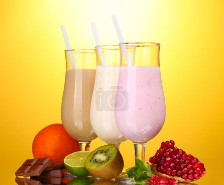 Milk shakes with fruits and chocolate on yellow ba...