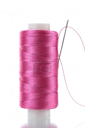 Pink bobbin thread with needle and sewing pin isolated on white