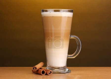 Fragrant сoffee latte in glass cup and cinnamon on wooden table on brown background
