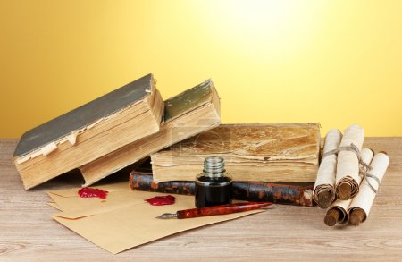 Old books, scrolls, ink pen and inkwell on wooden table on yellow background