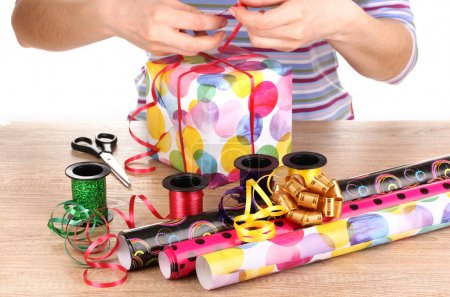 Wrapping presents surrounded by paper, ribbon and bows