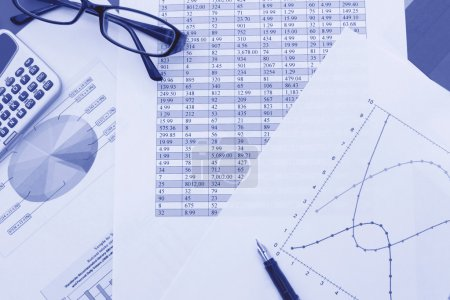 Photo pour Calculatrice et stylo en haut de divers graphiques et tableaux d'affaires - image libre de droit