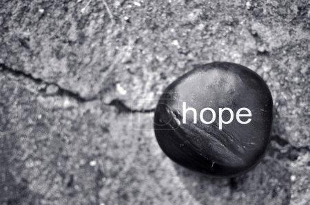 Photo pour Le mot espoir sur une pierre zen contre le béton - image libre de droit