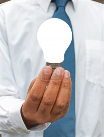 Photo for Businessman holding a lit bulb - Royalty Free Image