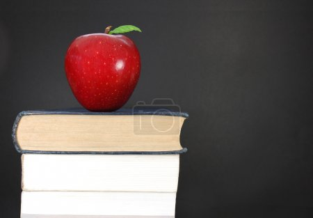 Photo for Stack of books and an apple next to a blank blackboard - Royalty Free Image