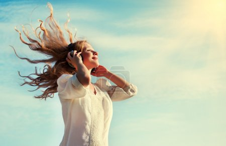 Photo for Beautiful girl with flying blond hair, listening to music on headphones in the sky - Royalty Free Image
