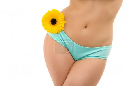A fragment of woman body in blue panties and yello...