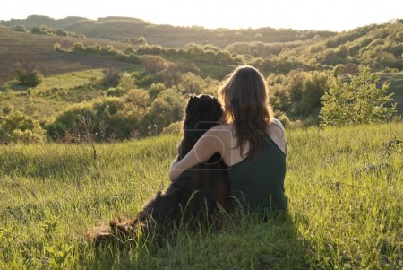 Photo pour Une belle jeune femme embrasse son chien comme ils sont assis dans un champ - image libre de droit