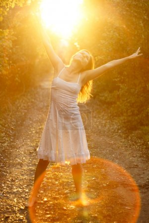 Foto de Chica guapa bailando en la luz dorada del sol poniente sobre pista forestal - Imagen libre de derechos