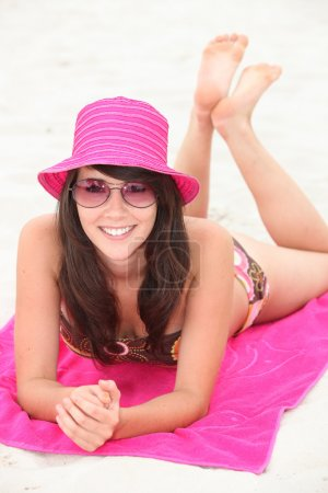 Attractive brunette laying on beach towel
