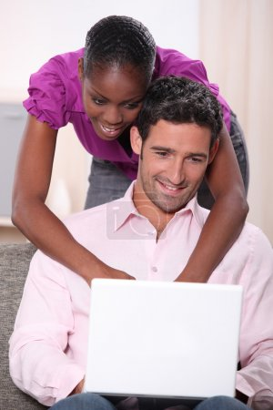 Black woman leaning on his boyfriend and doing computer laid on his boyfri