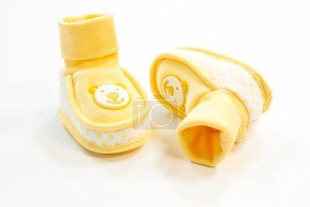 Photo pour Chaussons pour bébés jaunes à pois sur fond blanc - image libre de droit