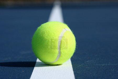 Photo pour Balle de tennis centré sur la ligne d'un tribunal moderne bleu - image libre de droit
